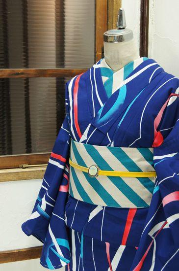 紺色地に赤・白・青のトリコロールカラーで染め出されたリボンのようなモダンデザインがスタイリッシュな注染レトロ浴衣です。