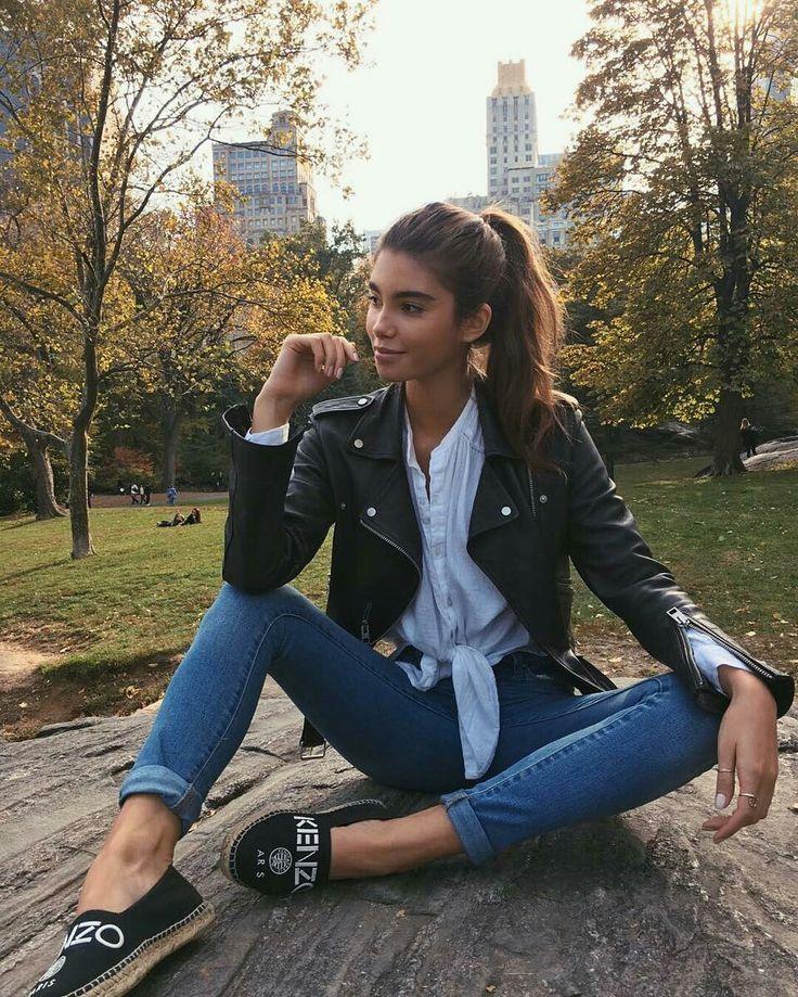 Jaqueta de couro, camisa com nó na cintura branca, calça jeans com barra dobrada, alpargata preta