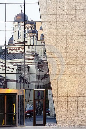 Old church building reflection on glass modern building facade.