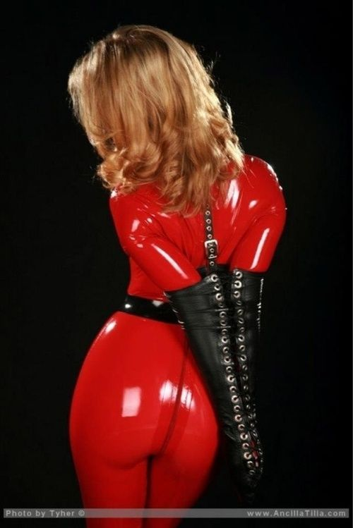 Ancilla Tilia in a red latex catsuit and armbinder. Photo ...