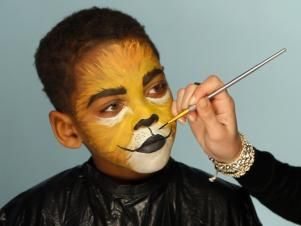 To give your child a ferocious lion's face for Halloween, simply paint a basic orange and yellow face. Then paint their top lip black and extend curving line up cheeks slightly. Paint their bottom lip black, then add black dots to white area above top lip. Add whiskers by brushing white paint in small, short strokes around mouth and cheek area.