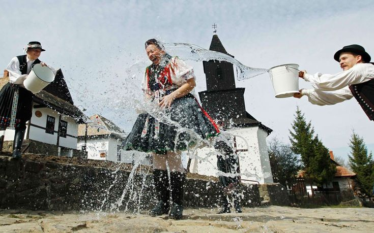 Men throw water onto a woman as part of traditional Easter celebrations in Holloko, Hungary. Locals from the World Heritage village of Holloko celebrate Easter with the tradition watering of the girls, a Hungarian tribal fertility ritual rooted in the area's pre-Christian past.