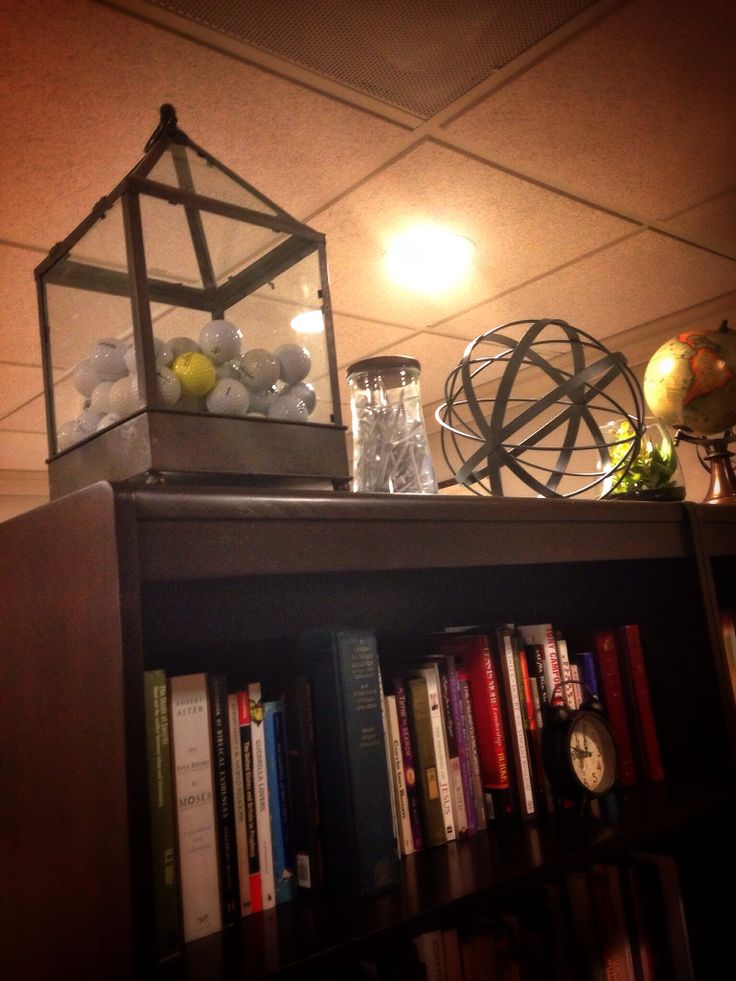 A Golfer's Man Cave for the Boss Man. Fill a glass container or, in this case, an atrium, with lots of golf balls. Mix of fun and function. by Janna Mascarin  #golf #golfdecor #mancave #library