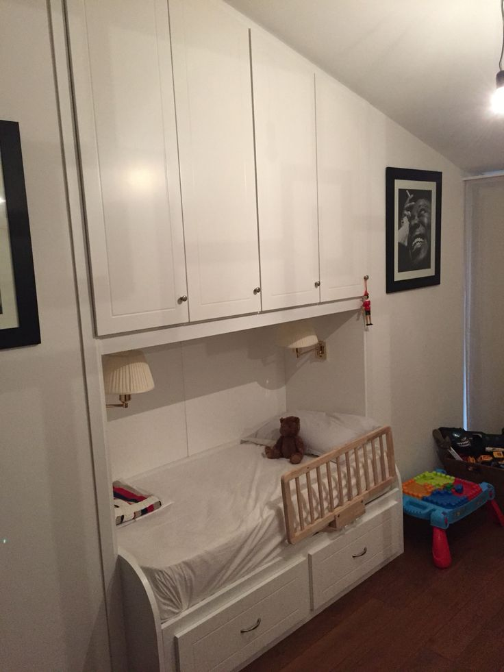 Armadio a ponte, laccato bianco, con la parte superiore in pendenza che segue il tetto. Sotto un letto per bambino, con cassettoni sottostanti. Tutto di nostra realizzazione.