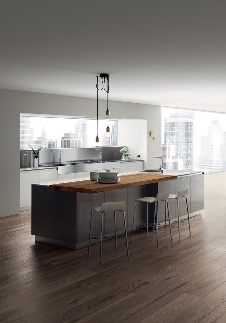 A trendy colour for this composition: stained look lacquered doors in Stained Steel for the island and cabinets, Light Grey matt lacquered doors for the work area and open-fronted tall units, stainless steel for worktops.