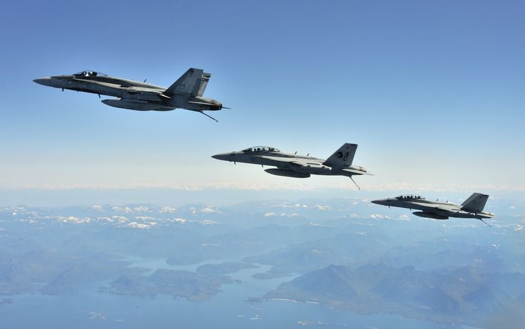 Near CFB Comox, British Columbia. 6 May 2013 - A Royal Canadian Air Force (RCAF) CF-18 Hornet fighter aircraft and two United States Navy F-18 Hornet fighter aircraft fly in formation in blue skies near Canadian Forces Base Comox British Columbia after they each completed an air-to-air refueling with a RCAF CC-130 Hercules on May 6, 2013 during Exercise TRIDENT FURY 13. (Photo by Sgt Norm McLean, Canadian Forces Combat Camera)