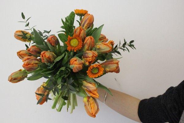 Orange Spring time flowers. Parrot Tulips, Calendula and Eucalyptus