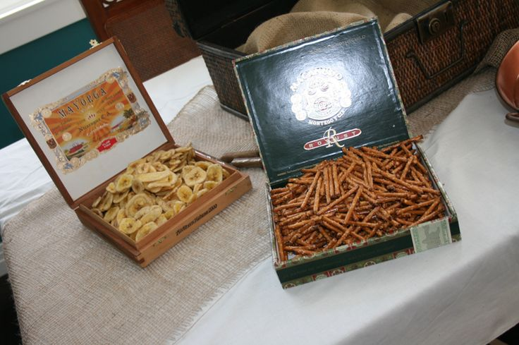 Cigar boxes with banana chips & pretzel sticks. Could be used as other decor on serving tables.