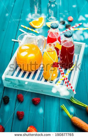 Fresh healthy homemade fruit juice squeezed from citrus, raspberries strawberries and carrots standing on a wooden tray in glass bottle on a turquoise picnic table in dappled summer sunlight - Shutterstock Premier