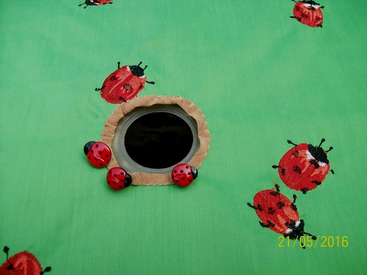Outdoor table cloth, with embroidered lady bug motifs and lady bug buttons applied to umbrella self-faced opening..