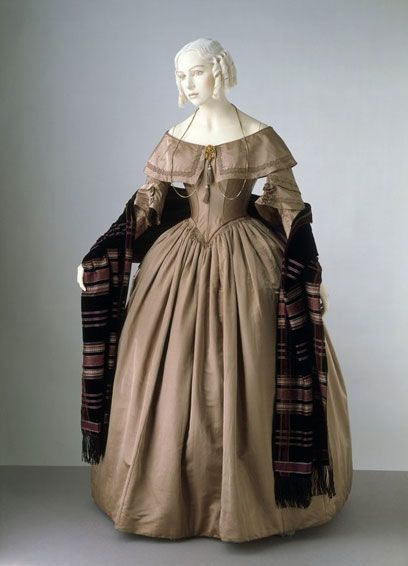 Victoria and Albert Museum: 1842, England; This dress is characteristic of fashionable styles from the early 1840s. The neckline is wide with a deep collar or 'bertha'. The long, tight sleeves are typical of the 1840s, while the short over-sleeves recall the elaborate sleeves of the 1830s. The waist is lengthened in front with a point both front and back. The elaborate applied decorations of the 1830s are now no longer fashionable.