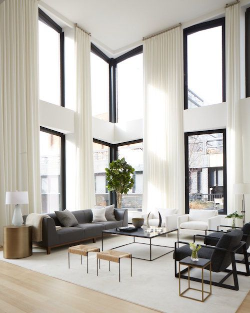 A neutral palette and floor-to-ceiling curtains highlight the massive windows in this ASH NYC–designed Manhattan duplex, which is next to the High Line.