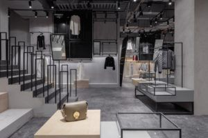 Milky white textured walls and white floor create a clean and white space. Bamboo poles are set up and hemp rope is used to connect them, clothes racks are thus formed.