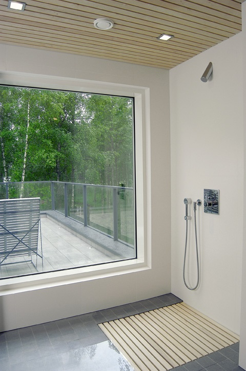 Lovely bathroom with a large window and Il Bagno Alessi One by Oras shower faucet.