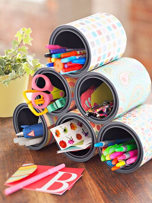 Take extra cans, cover in scrapbooking paper, and hot glue into a pyramid to create an easy and beautiful extras holder for your dorm room desk!