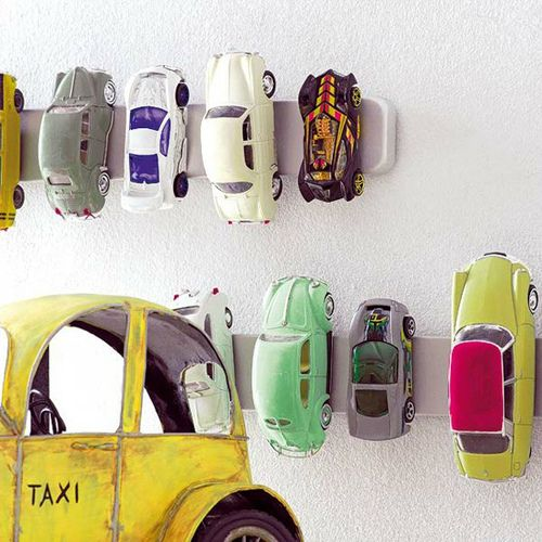 Use an IKEA magnetic knife rack as a garage for toy cars! Cute way to organize.