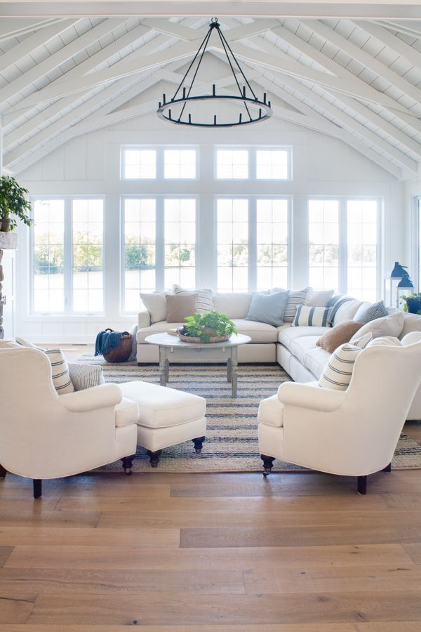 Lake house living room decor featuring white board and batten walls a striped jute rug comfy white couches and a rustic mantel you can get additional