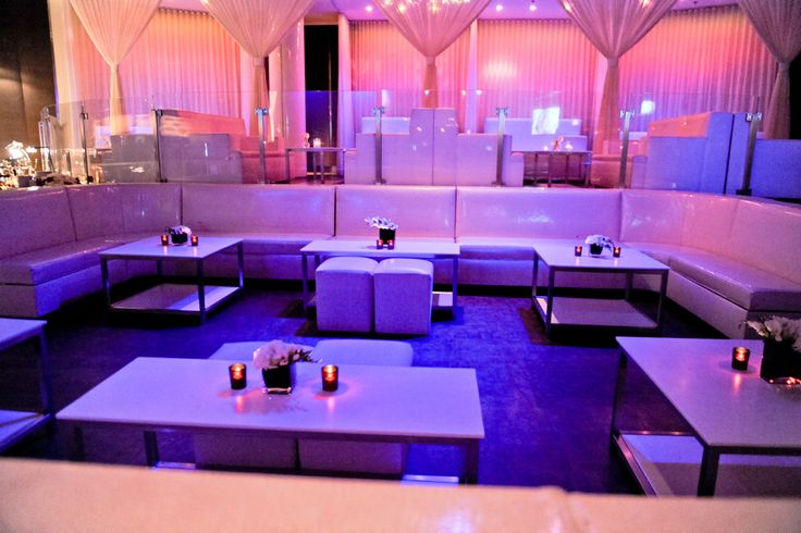 nightclub wedding-obviously our club is much prettier but I like the idea of the small arrangements and candles on lounge tables as well as again- the purple and pink lighting