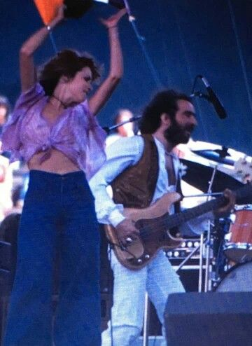 Stevie wearing jeans ~ flared jeans !!! and a filmy knotted top, showing her belly with John Mcvie onstage ~ Stevie's energetic arms and tambo actions as well as her twirling  had already become her signature moves during the late '70's    ♫☆♥❤♥☆♫