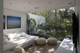 Bedroom with natural materials and light, with windows framing view.