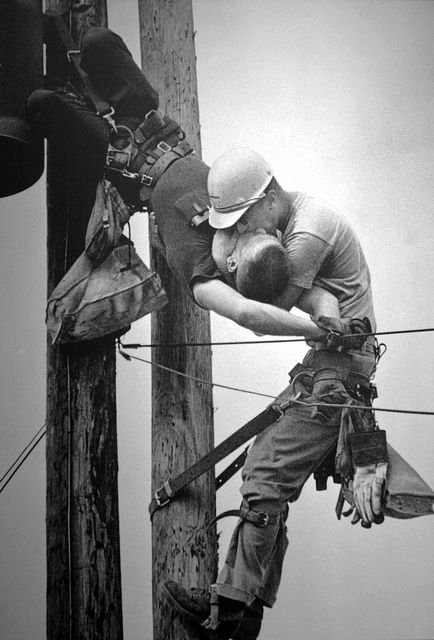 """The Kiss of Life    1968 Pulitzer Prize, Spot News Photography, Rocco Morabito, Jacksonville Journal    July 17, 1967: Air conditioners hum all over Horida. In Jacksonville, they overwhelm the electrical system and knock out the power. Jacksonville Journal photographer Rocco Morabito is on his way to photograph a railroad strike when he notices Jacksonville Electric Authority linemen high up on the poles. """"I passed these men working and went on to my assignment,"""" says Morabito. """"I took eight…"""