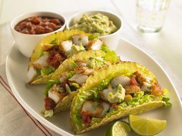 Fisch-Tacos mit Limette und Koriander: Saftiger Kabeljau auf einem Salatbett, serviert in einem warmen, knusprigen Taco mit Salsa und Guacamole – einfach lecker!