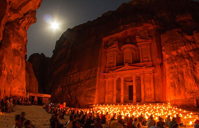 Travellers gather around the Al Khaznet temple at night with candles.