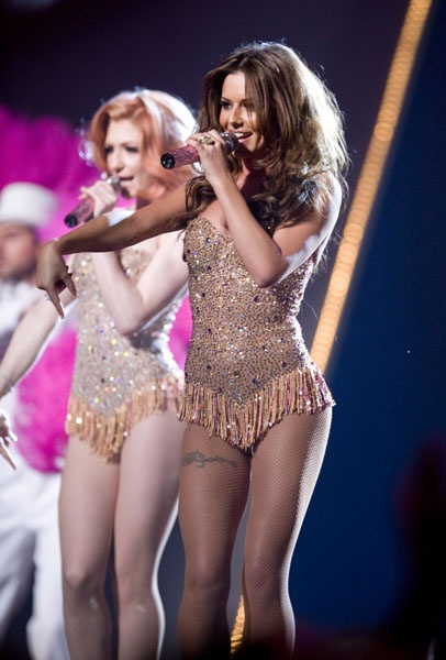 cheryl cole performing on stage with girls aloud nicola roberts in fringed sparkly playsuit
