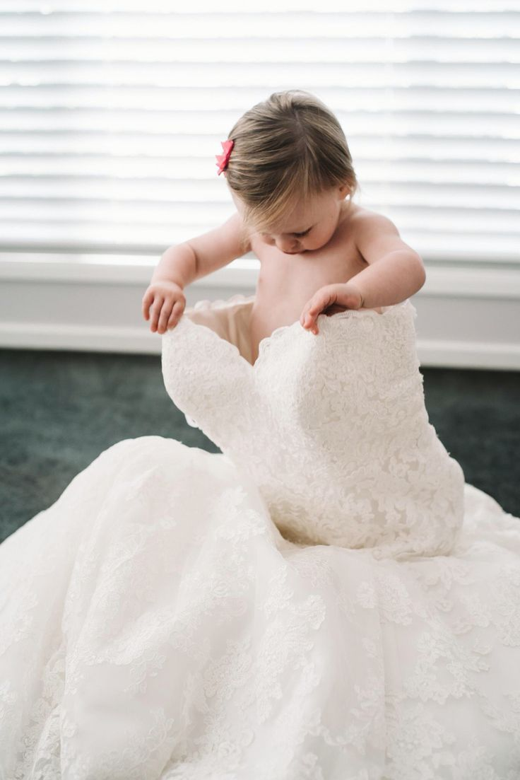 Daughter in her mothers wedding dress. Toddler playing in wedding dress.