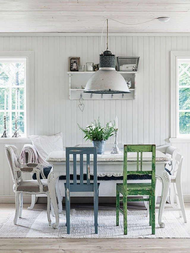 What a wonderful look, those bright chairs in an all white room. Wonderful industrial lamp too.