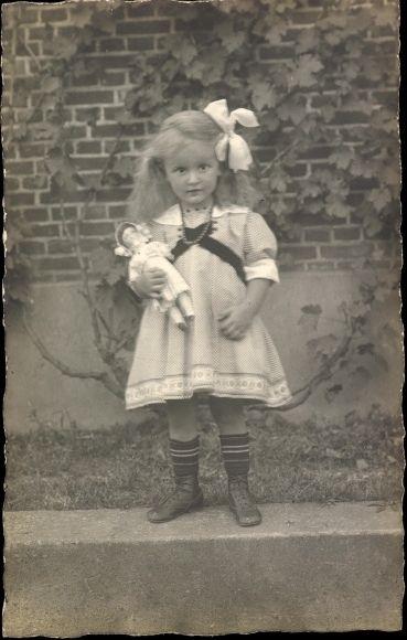 Foto Ak Kleines Mädchen in weißem Kleid, Haarschleife, Puppe, Spielzeug