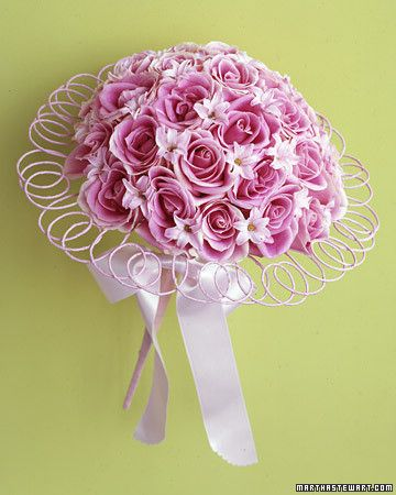 A stylish nosegay achieves its perfect domed shape with wired pink roses and hyacinth blossoms with yellow floral pins at their centers. Wire wrapped in pale-pink ribbon is a lighthearted accent that frames the bouquet.
