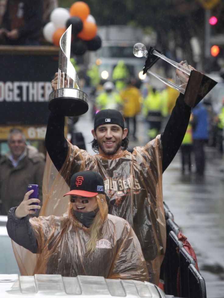 Madison Bumgarner raises his MVP trophies while his wife Ali shoots a selfie during the parade. Photo: Paul Chinn