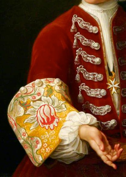Large upturned cuff of floral painted silke with three silver buttons, of a red velvet frock coat with silver thread worked frogging with silver tassels and silver buttons. Plain white stock and shirt, with plain ruffles at wrist. Cross is the Order of St John. Detail from Young Knight of the Order of St John, c.1730, by Antonio David.