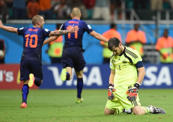 Spain's goalkeeper Iker Casillas, right, reacts after Netherlands' forward Arjen Robben, back center, and Netherlands' midfielder Wesley Sneijder celebrate after Robben scored his team's fifth goal during the football match between Spain and the Netherlands at the Fonte Nova Arena.