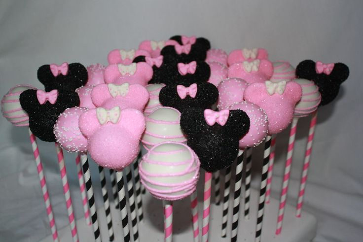 Pink Minnie Mouse cake pops on paper straws.