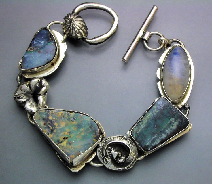 """, """"Opal and Moonstone Bracelet"""" A sterling silver bracelet with three colorful boulder opals , an iridescent moonstone and hand fabricated silver elements. Seven inches in length."""