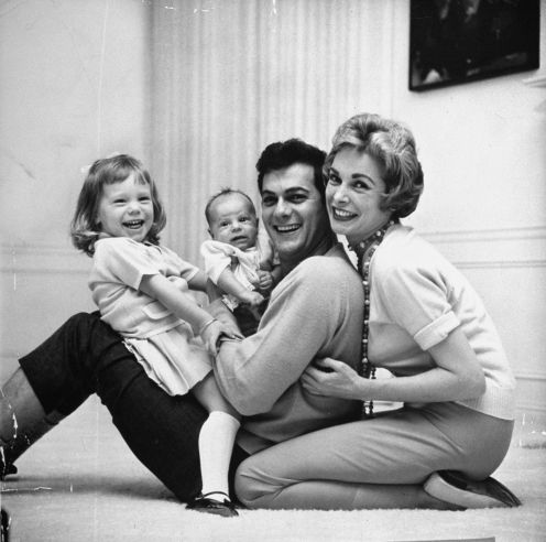Screen icons Tony Curtis and Janet Leigh play with their daughters, future TV actress Kelly Curtis, left, and future movie star Jamie Lee Curtis in their Beverly Hills Home in 1959.