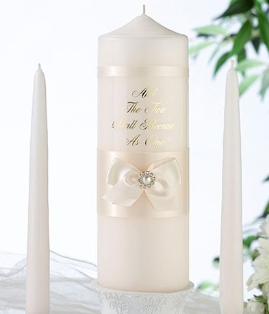 "- This stunning ivory pearl candle set is beautifully decorated with ivory satin ribbons and bow with a pearl/rhinestone accent.  Pillar has a gold verse "" And The Two Shall Become As One"" Set includes one 9"" pillar and two 10"" tapers."