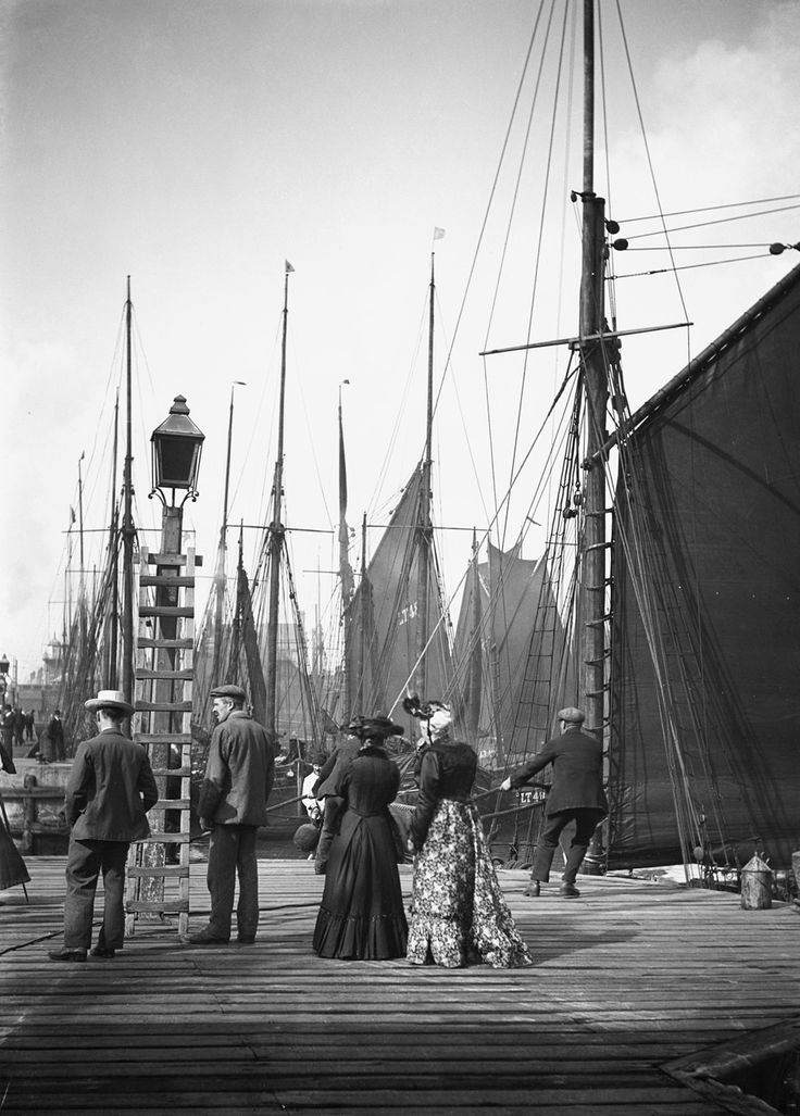 Men and women onlookers at the end of the quay looking at the forest of masts and sails in the harbour. - National Maritime Museum