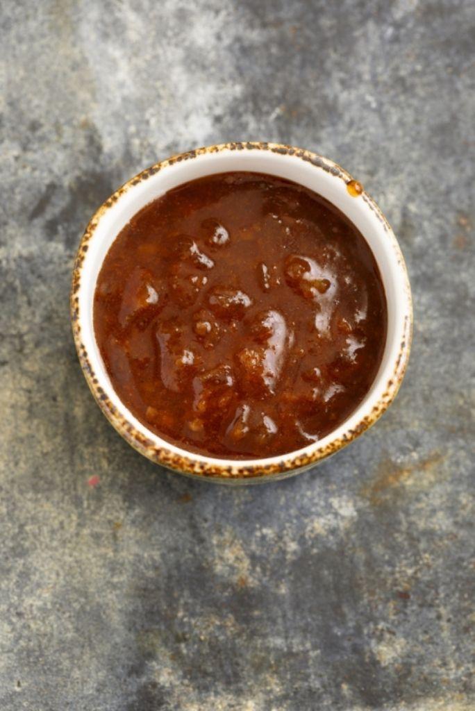Bereiden: Stoof de sjalot aan in een klontje boter. Doe er de laurier en het gepelde teentje look bij. Blus met een scheut cognac. Giet de rode wijn erbij en kook in voor de helft. Doe de kalfsfond erbij en laat 10 minuten suddderen op een laag vuurtje. Roer beetje bij beetje de koude boter door de saus en breng op smaak met zwarte peper.