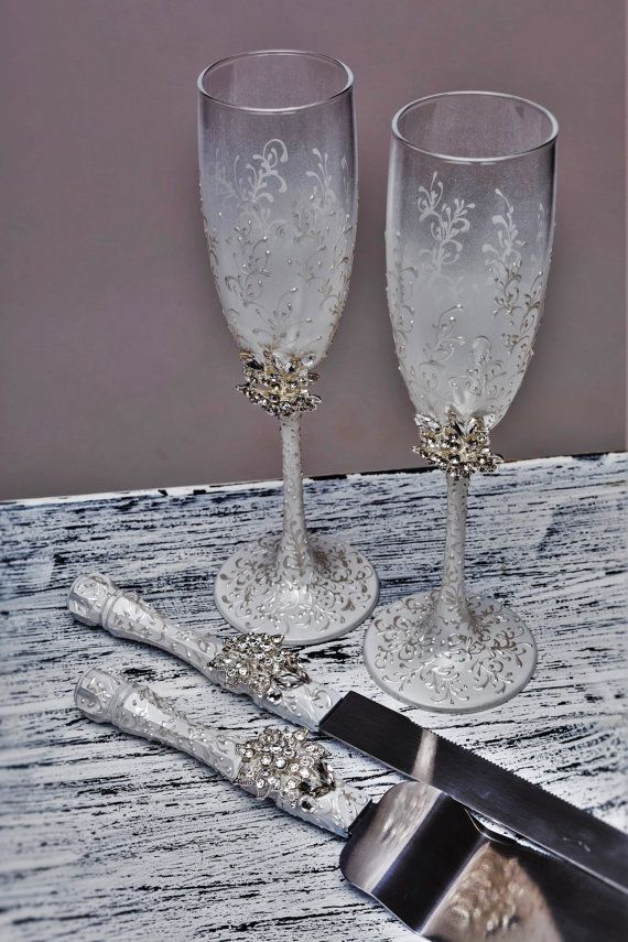 Personalized Wedding glasses Toasting flutes white and silver Champagne glasses personalized laser engraved Champagne flutes set of 2  This set includes 2 flutes For these glasses color: white paint and silver crystals and rhinestones  All completely handmade! MEASUREMENTS: -Champagne flutes : Height - 9.2 inch (23.5 sm). Volume – 170ml (6.1 oz)  Custom champagne glasses may be created to fit your needs. Your unique wedding colors can be used for this design. Names and date may be painted to…