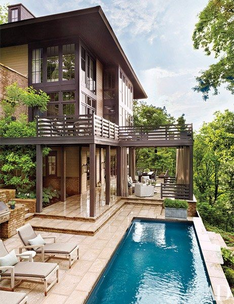 The rear exterior of a Nashville home where chaise lounges cushioned with a Sunbrella fabric are positioned next to the pool | archdigest.com