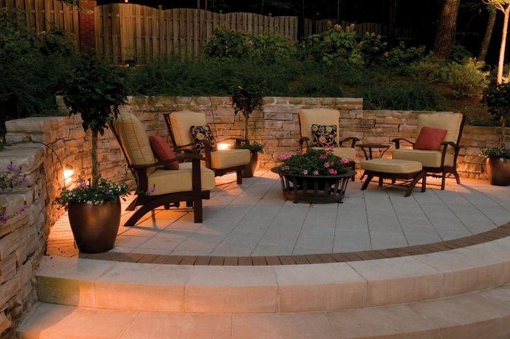 terrasse carrelée avec mobilier élégant et muret de soutènement en pierre décoré d'appliques solaires