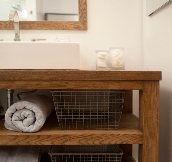 Modern rustic bathroom with teak washstand with white over-mount vessel sink and polished nickel ...