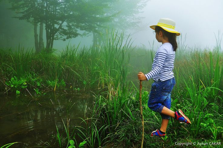 Waiting for Mysterious Lake Monster by NATIONAL SUGRAPHIC Betül İpek in Wonderland Series Fog and Little Girl with Yellow Hat around the Lake Keremali. Çamlıca Village Hendek District Sakarya Province New Turkei. NATIONAL SUGRAPHIC Always Under The Li