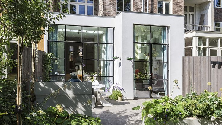 Deze aanbouw met zwart stalen pui en daklichten brengt veel licht in de woning. De moderne strakke uitstraling zorgt voor een krachtig contrast met de woning. Ontwerp: BNLA architecten. Fotografie: Wim Hanenberg.