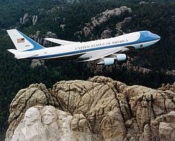 "SAM 28000, 1 of 2 VC-25s used as Air Force One,  over Mount Rushmore in Feb. 2003.    The idea of designating specific military aircraft to transport the President arose in 1943.   The ""Air Force One"" call sign was created after a 1953 incident during which a flight carrying President Dwight D. Eisenhower entered the same airspace as a commercial airline flight using the same call sign."