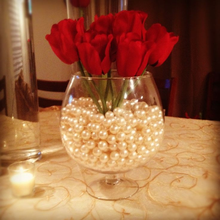Ivory Pearls and Red Tulips in a oversize champagne vase.. A classy centerpiece for you, friends and family members wedding reception or special event.. #ManeEventDesign..