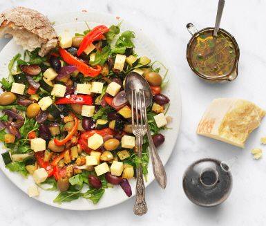 Ugnsrostade grönsaker ger färg till den här ostsalladen som går lika bra att servera ljummen som kall. Välj en lagrad hårdost med mycket smak som matchar stingig rucola och oliver med sälta. En matig sallad med medelhavstoner som är perfekt som lunchrätt eller på en buffé.